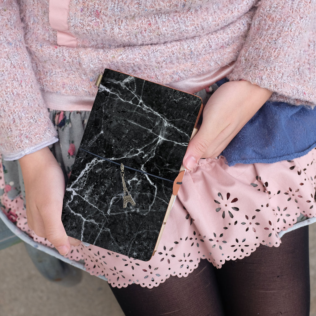 a young girl showing midori style traveler's notebook with moody marble design above her leg
