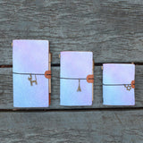 three sizes of midori style traveler's notebook with ombre pastel galaxy design on the wooden bench