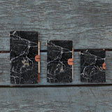 three sizes of midori style traveler's notebook with moody marble design on the wooden bench