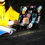 a girl using macbook air with personalized Macbook carry bag case with Black Flower design on a wooden table