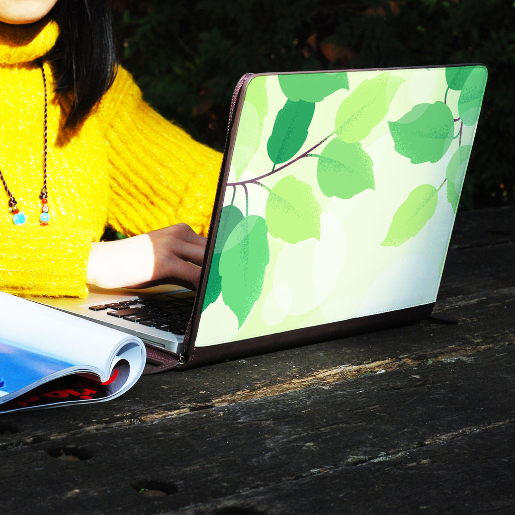a girl using macbook air with personalized Macbook carry bag case with Leaves design on a wooden table