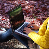 a girl typing on macbook air with personalized Macbook carry bag case with Leaves design