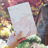 a girl holding personalized RFID blocking passport travel wallet with Pink Marble design