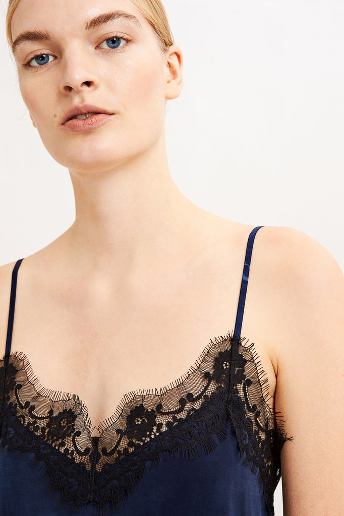 This delicate camisole top has been cut from a draping cupro jersey fabric. A floral lace border trims the neckline and hems while adjustable spaghetti straps complete this camisole top.  Fabric - 92% Cupro 8% Spandex