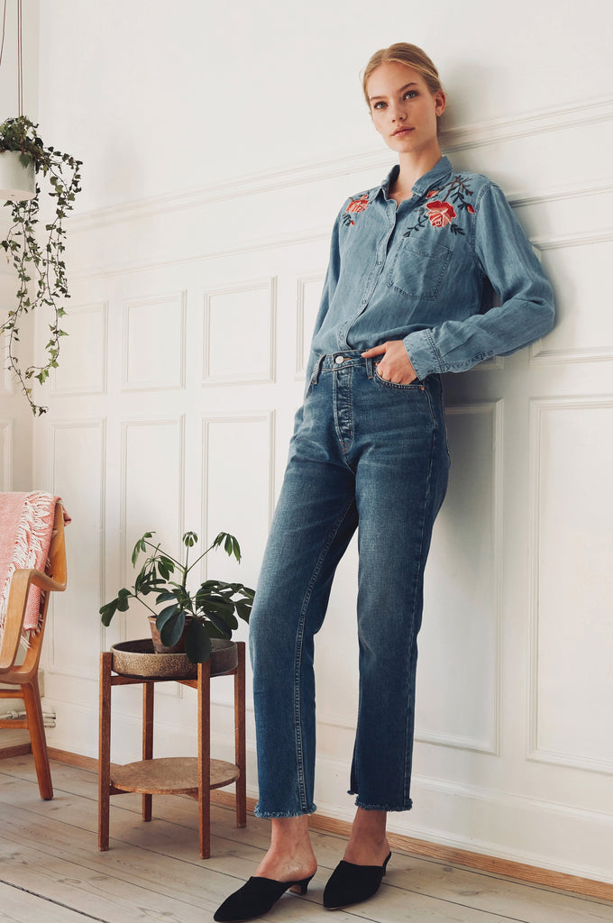 Long sleeve, denim button-down top with single chest pocket and floral embroidery detail on top front of shirt.