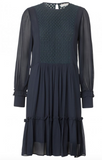 Short dress in light viscose georgette with long sleeves and ruffles at the skirt and wrist. The dress has a pattern at the chest and round neck. Use the dress with sandals or high boots.