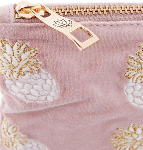 Inspired by the tropical pineapples sold in Saint -Tropez market, this travel pouch is designed to encourage fun and imagination. Featuring hand illustrated gold and white pineapples embroidered onto a mauve coloured velvet fabric. This bag includes a gold zip with an embossed lotus flower, symbolising peace and purity.