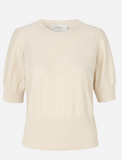 This short sleeved knit from Munthe features ribbing around the neckline, hem and sleeves.  There is a delicate hole-knit detail that makes this jumper unique.  Pair with a pretty skirt or your favourite denim.