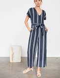 Short sleeve, heavy luxe linen, wide leg striped navy jumpsuit with V-neckline, removable belt, and side pockets. Center back zipper. Throw on and go for an easy one-and-done look.