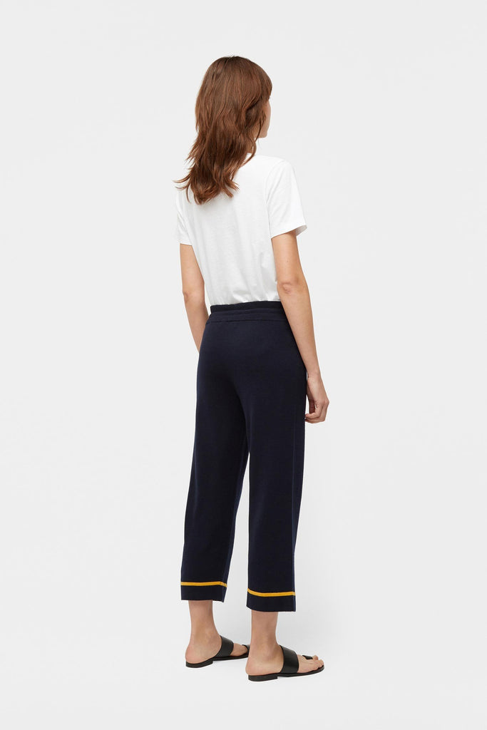 "The epitome of casual elegance, this 100% cashmere navy cropped lounge pant is detailed with a contrast stripe in sunny mustard yellow to the hem.   Styled with the White Cocktail T-Shirt Made in London, UK 100% cashmere Regular fit, crop length Navy, mustard yellow stripe Model is 5'10"" and wears a size small"