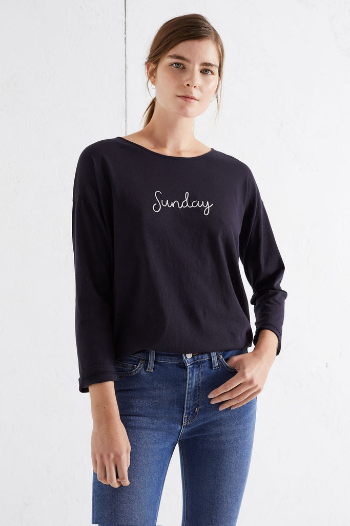"Capturing the laidback spirit of the weekend, this boxy-fit navy cotton t-shirt is an easy and flattering choice for Sundays. 100% cotton Boxy fit, crew neck Made in Portugal Navy, ivory embroidered letters Model is 5'10"" and wears a size small"