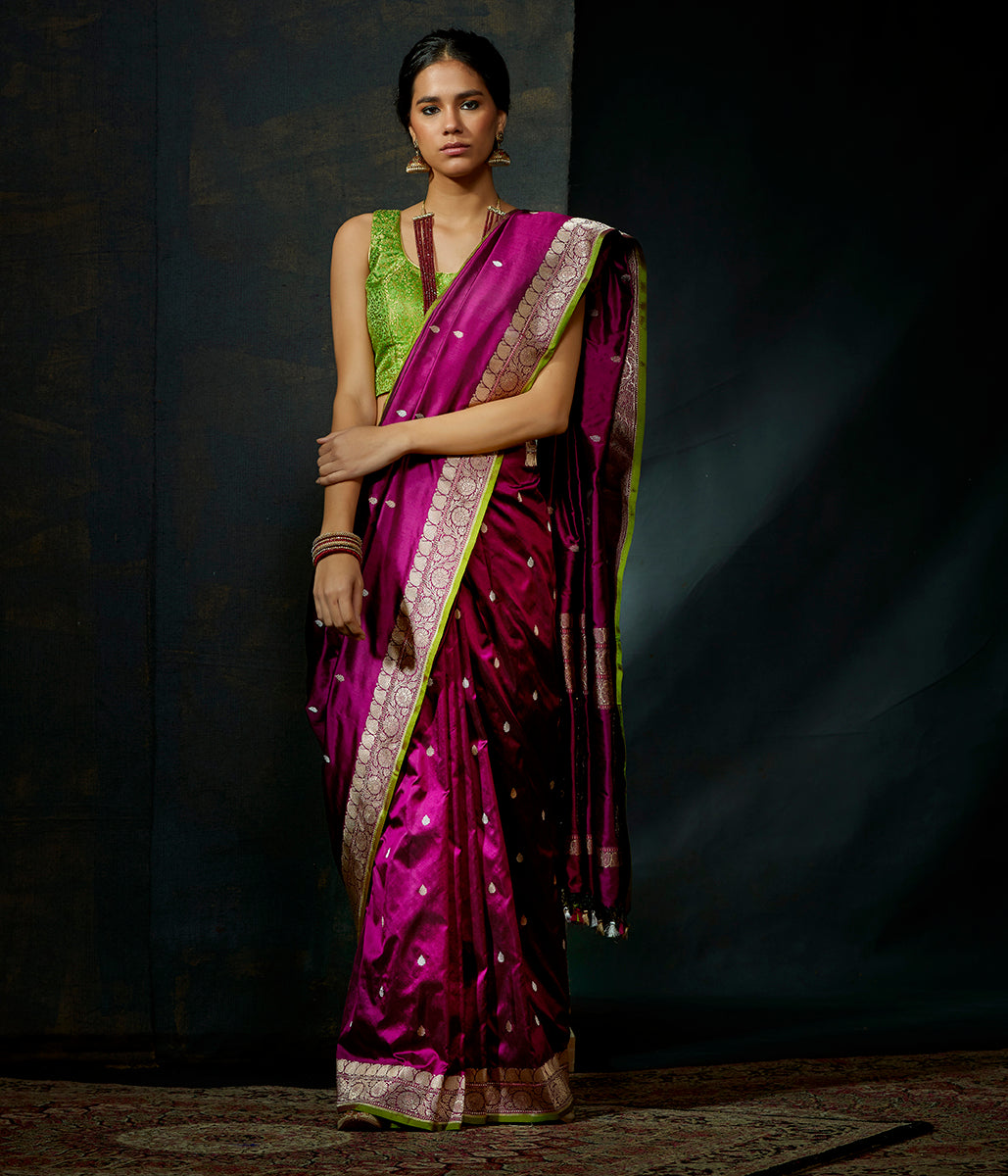 Purple kadhwa booti saree with green selvedge and floral motifs on pallu