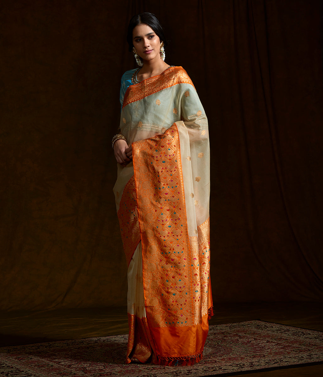 Beige banarasi kora silk saree with kadhwa booti and kadhiyal orange border