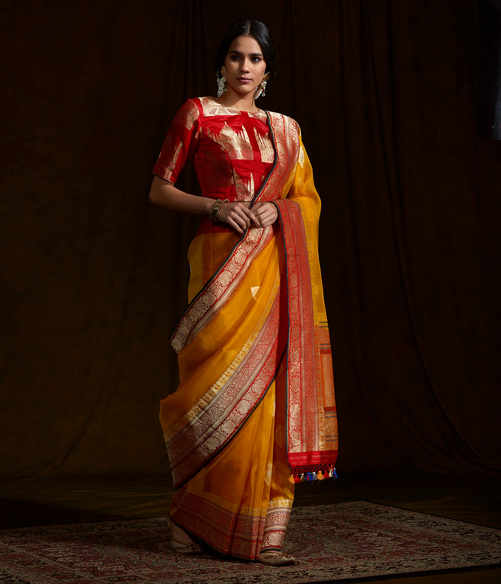 Yellow banarasi kora silk saree with red border and pallu and black selvedge