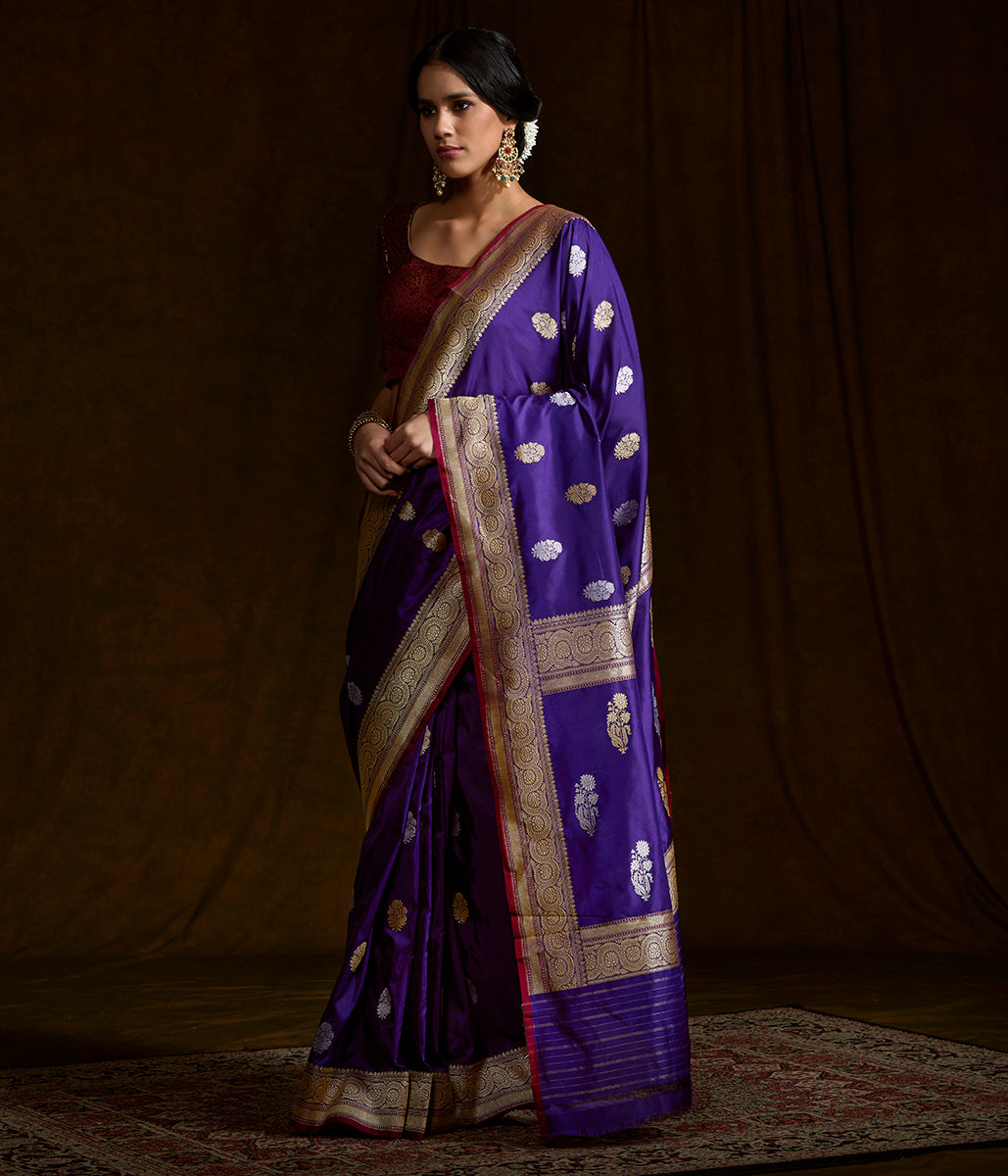 Purple katan silk saree with floral motifs and a delicate kadhwa border with a deep pink selvedge