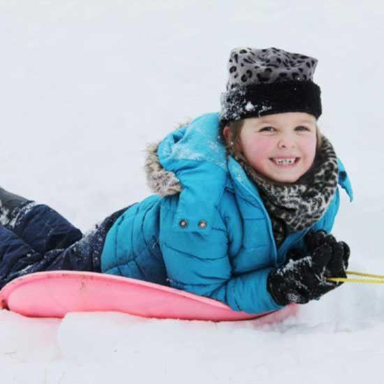 Little girl sledding in home made neck warmer