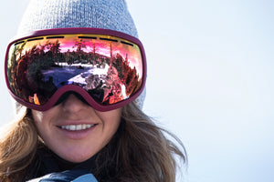 girl wearing a grey beanie and pink snow goggles