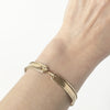 A solid 10K yellow gold ridged bangle. Bracelet has a hook closure, which is a both  unique and functional element.