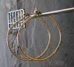 gold hoop earrings hanging in fron of gray stone