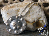 silver and black pendant with dots in front of light rock
