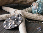 sideview of silver and black pendant necklace on white starfish