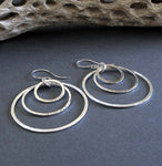 Sterling silver 3 ring dangle earrings on gray background