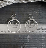 Three circles silver earrings shown on gray stone with a metric ruler