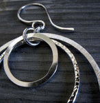 Close up of silver earring with 3 rings and different textures