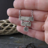 Inverted pyramid silver pendant necklace shown in hand