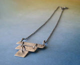 Silver strips pendant necklace shown on blue to tan gradient background