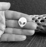 silver alien tie tack pin held in hand with driftwood black and white