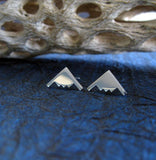 Tiny silver b2 bomber stud earrings on blue background with driftwood
