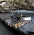 silver cat face ring on rock with driftwood