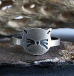 cat face ring with whiskers on rock with driftwood