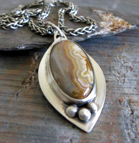 Sterling Silver marquise pendant with sand colored gemstone on gray stone