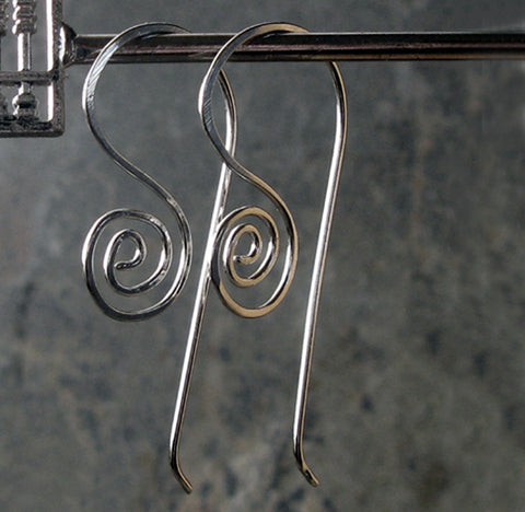 wire silver spiral earrings hanging on gray background