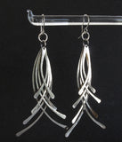 hanging silver earrings on black background