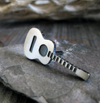 Acoustic Guitar tie tack pin on gray stone with driftwood