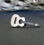 Acoustic Guitar tie tack pin on gray background with driftwood