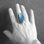 Oval Labradorite Gemstone Statement Ring on hand with black background