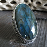 Oval Labradorite Gemstone Sterling Silver Ring on gray stone
