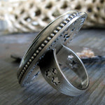 Side View of Ring With Star cut outs in band tree branch in background