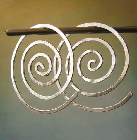Spiral hoop earrings on gradient background