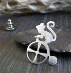 Silver Circus Monkey on Tricycle tie tack pin on dark background with driftwood