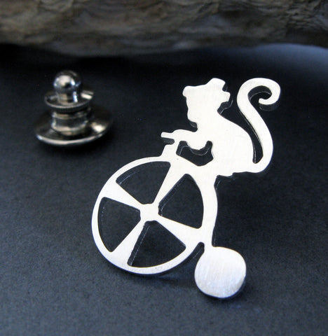 Silver Circus Monkey on Tricycle tie tack pin on dark background