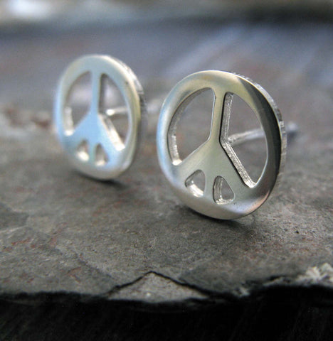 silver peace sign stud earrings on a gray rock