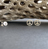 silver peace sign stud earring on gray with driftwood
