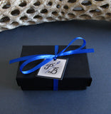 black cardboard jewelry box with blue ribbon and white tag PB