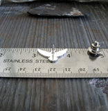 flying raven silver pin shown on ruler and gray stone