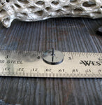 round black tie tack on a ruler with driftwood background